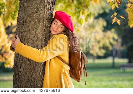 Smiling girl with closed eyes hugging tree at park during autumn season. Beautiful woman hugging a tree. woman embracing a tree trunk with a blissful expression: environmental conservation.