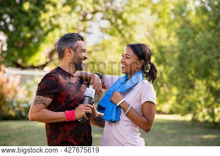 Cheerful multiethnic couple resting together after jogging in the park. Happy mature man and beautiful woman laughing while resting after running. Woman and indian man taking a break after fitness.