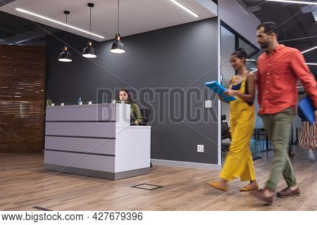 Two diverse creative colleagues walking holding documents and smiling. modern office of a creative design business.