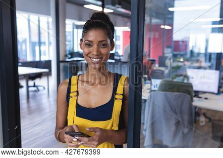 Portrait of mixed race female creative worker using smartphone and smiling. modern office of a creative design business.
