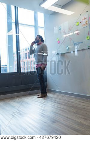Mixed race male creative worker talking on smartphone standing next to window. modern office of a creative design business.