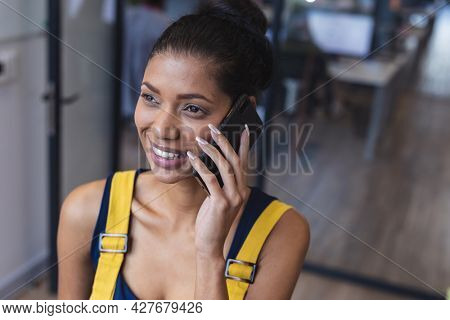 Mixed race female creative worker talking on smartphone and smiling. modern office of a creative design business.