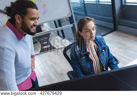 Two diverse creative colleagues sitting at desk using computer and smiling. modern office of a creative design business.