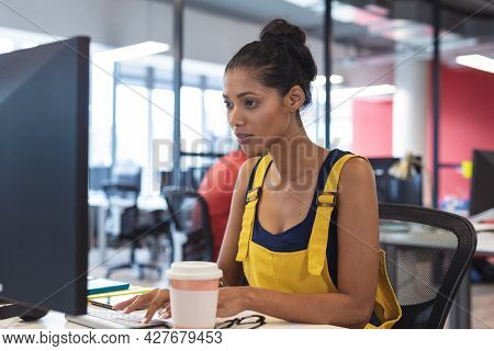 Mixed race female creative worker sitting at desk using computer. modern office of a creative design business.