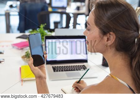 Caucasian female creative worker sitting at desk using smartphone taking notes. modern office of a creative design business.