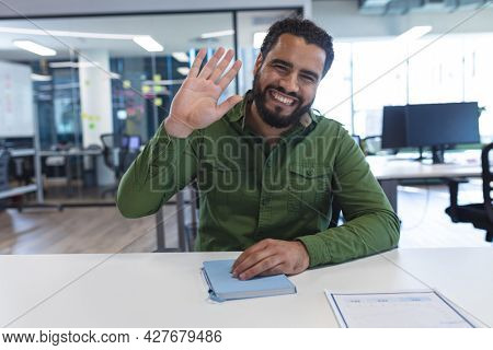 Portrait of mixed race male creative worker sitting at desk looking at camera. modern office of a creative design business.