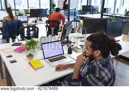 Mixed race male creative worker sitting at desk using laptop. modern office of a creative design business.