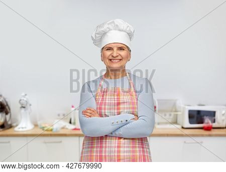 cooking, culinary and old people concept - portrait of smiling senior woman or chef in toque in apron with crossed arms over kitchen background