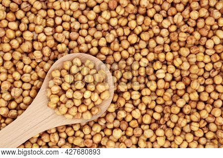 Spicy roasted organic chickpeas for a healthy snack in a wooden spoon and forming a background. High in fibre, protein, vitamins and minerals. Flat lay.