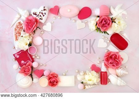 Beauty spa treatment products for skin and body care with rose and freesia flowers forming an abstract background border. Natural health care concept. Flat lay on mottled pink.