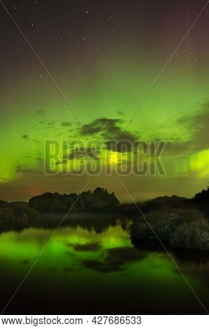 Aurora Borealis Northern Lights Over The River. Aurora Borealis In The Night Sky. Purple And Green N