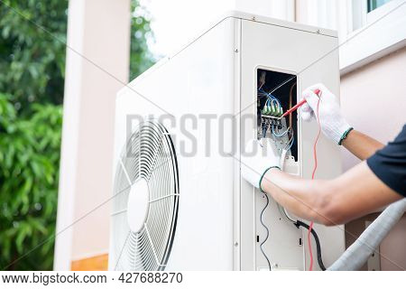 Technician Using Measuring Equipment Checking Electric At Circuit Breaker On Outdoor Air Compressor