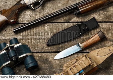 Hunting Equipment On Old Wooden Background Including Rifle, Knife, Binoculars And Cartridges