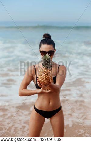 Beautiful Woman With Bronze Tan In Bikini Holds Pineapples In Hands