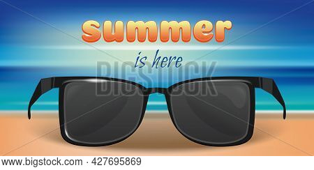 Sunglasses In The Sand On The Background Of The Sea Or The Ocean. Summer Is Here. Summer Concept Des