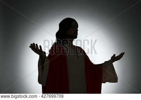 Silhouette Of Jesus Christ With Outstretched Arms On Color Background