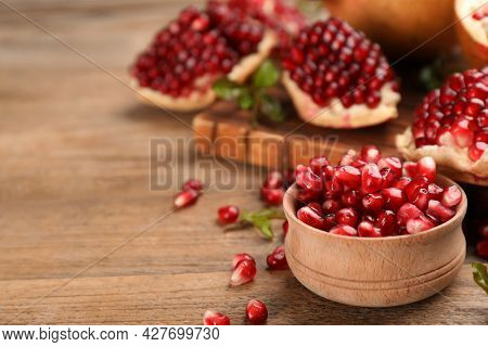 Delicious Ripe Pomegranate Kernels In Bowl On Wooden Table. Space For Text