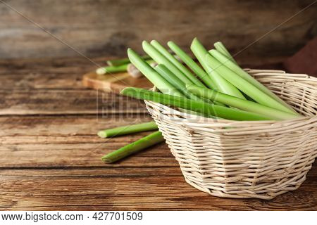 Fresh Lemongrass In Wicker Bowl On Wooden Table, Space For Text