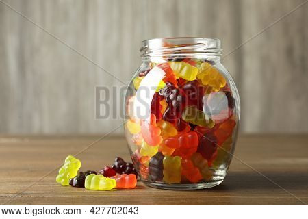 Delicious Gummy Bear Candies In Jar On Wooden Table