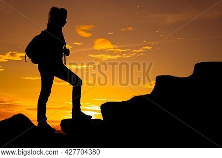 Woman Walking On Top Of Mountain At Twilight With Backpack