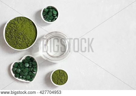 Chlorella Green Powder, Spirulina Pills And A Glass Of Water On A White Background. Superfood. Vegan
