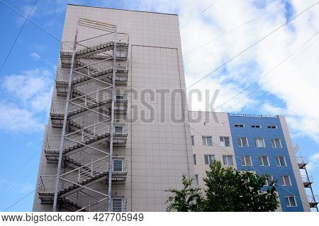Modern Residential Building With A Fire Escape Against A Blue Sky With Clouds. Fire Escape Stairs On