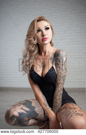 A Slender Woman In A Tattoo In A Short Dress A Sexy Dress With A Large Silicone Breast Poses Against