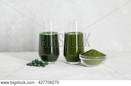 Chlorella And Spirulina Green Drinks On A White Concrete Background. Spirulina Tablets And Chlorella