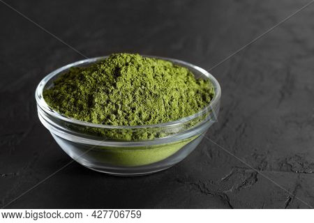 Chlorella Green Powder In A Bowl On A Black Background. Seaweed Natural Supplement. Spirulina Powder