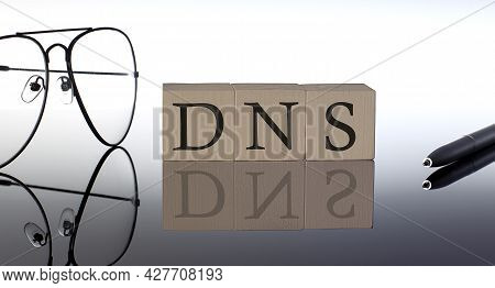 Close-up Of Dns Wooden Blocks On Black Background With Glasses And Pen
