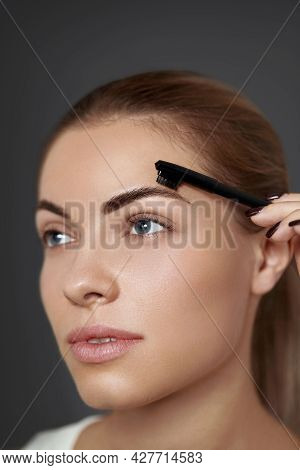 Eyebrow Makeup. Beautiful Woman Shaping Brows With Comb   Closeup. Beauty Girl Model With Profession