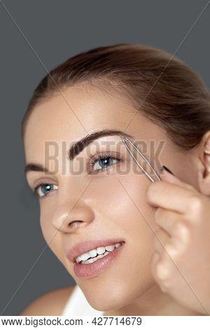 Tweezing Eyebrows. Eyebrow Correction.  Plucking Eyebrows. Beautiful Young Woman With Tweezers. Mode