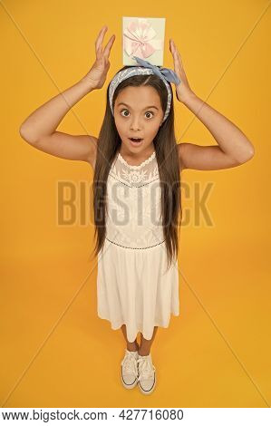 Present Makes Holidays Special. Surprised Child Hold Gift Box On Head. Happy Birthday. Holiday Celeb