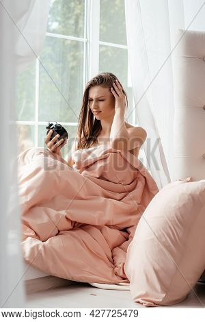 Young Woman Lying In Bed Suffering From Alarm Clock Sound Covering Head Making Unpleasant Face. Inso