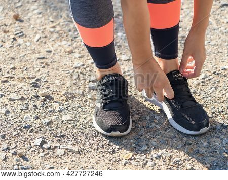 Suphan Buri, Thailand - July 24, 2021: Hands Tying Shoelaces Of Running Shoes And Legs Woman Standin