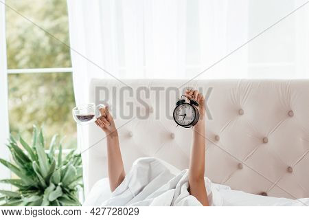 Wake Up Female Hand Showing Coffee Cup And Alarm Clock In On Bed In Bed Room. Young Girl With Two Ha