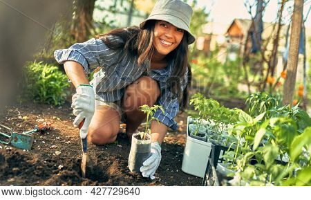 Positive Female Gardener Working With A Trowel In The Garden To Growing New Plants. A Young Woman Pl