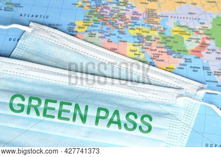 Surgìcal Masks With Text Green Pass Over A Geographical Map. Safe Travel Concept During Coronavirus
