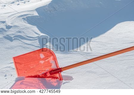 A Snow Shovel Is Stuck In A Snowdrift In Winter In Winter. Snow Removal, Cleaning The Street From Sn