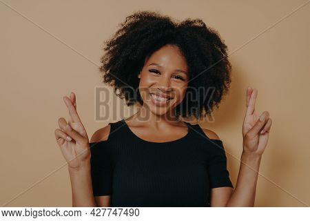 Portrait Of Happy Young African Woman Standing Isolated Over Dark Beige Studio Background With Copy