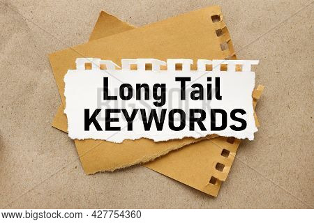 Long Tail Keywords, White Torn Paper On Brown Torn Paper Background. Craft Background