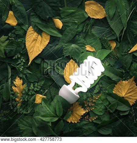Vibrant green foliage with gold leaves lit by energy efficient lightbulb. Concept of environmentally friendly ideas, energy efficiency, or eco friendly thinking.