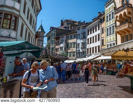 Bolzano, Italy, June 2021. At The Local Market Two Tourists Are Consulting The Tourist Map. One Poin