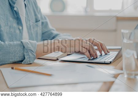 Cropped Shot Of Man Using Laptop Computer At Home, Male Hands Typing On Keyboard On Kitchen Table. C