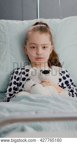 Portrait Of Lonely Little Child Looking Into Camera Holding Teedy Bear In Hands Resting In Bed Suffe