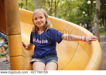 Charming Happy Girl Sliding On Playground Slide, Smiling To The Camera
