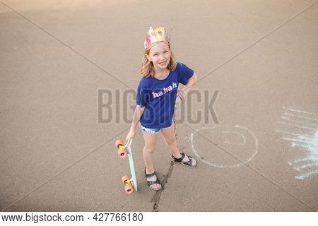 Top View Full Length Shot Of A Cheerful Young Girl Smiling To The Camera, Standing With Her Pennyboa