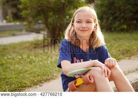 Charming Happy Young Girl Looking Away Cheerfully, Sitting With Her Pennyboard
