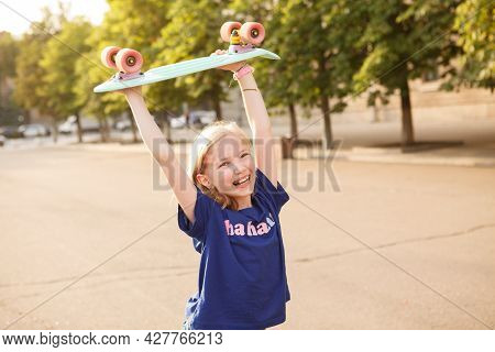 Happy Young Girl Laughing, Holding Up Her Pennyboard In The Air