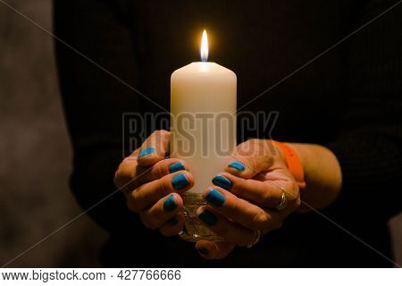 A White Candle Burning With Warm Yellow Light. The Light Illuminates The Female Hands Holding The Ca